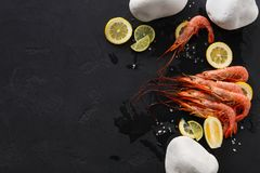 Shrimps with lemon and stones on black background Royalty Free Stock Photos