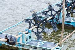 At shrimps pond in the rainy season,and paddle wheel aerator Stock Photo