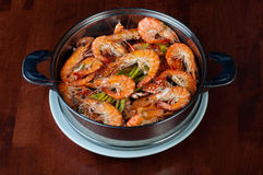 Shrimps in a pot. Boiled shrimp with vegetables in a pot on wooden table Stock Images