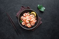 Shrimps, Prawns. In bowl, top view, copy space. Fresh seafood ingredient - shrimp tails on black. Boiled prawns and chopsticks stock image