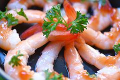 Shrimps prawns seafood cooked on hot pan with curly parsley and ketchup on dark plate stock image