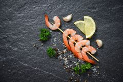 Shrimps prawns in skewer sticks seafood cooked herbs and spices on dark background stock image