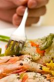 Shrimps and rice. Hand with fork starining after some rice, vegetables and shrimps on the white plate Stock Images