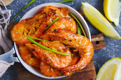 Shrimps roasted on frying pan with lemon and garlic. Royalty Free Stock Image