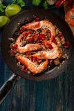 Shrimps roasted on frying pan with onion, garlic and chili Royalty Free Stock Photos