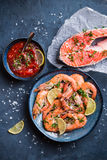 Shrimps and salmon background. Salmon and shrimps on plate with lemon, salt, sauce. Fish and seafood concept. Close-up. Top view. Big red prawns and salmon for Stock Images