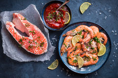 Shrimps and salmon background. Salmon and shrimps on plate with lemon, salt, sauce. Fish and seafood concept. Close-up. Top view. Big red prawns and salmon for Stock Photography