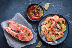 Shrimps and salmon background. Salmon and shrimps on plate with lemon, salt, sauce. Fish and seafood concept. Close-up. Top view. Big red prawns and salmon for Royalty Free Stock Image