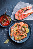 Shrimps and salmon background. Salmon and shrimps on plate with lemon, salt, sauce. Fish and seafood concept. Close-up. Top view. Big red prawns and salmon for Stock Image