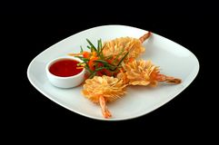 Shrimps with sauce on a white dish. On a black background stock photos