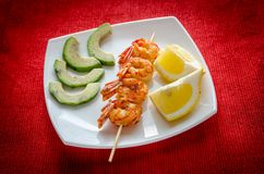 Shrimps skewers with avocado and lemon slices Royalty Free Stock Photos
