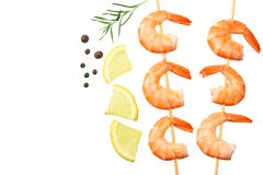 Shrimps skewers with lemon and rosemary isolated on a white background. top view stock photography