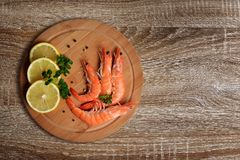Shrimps on cutting board. Shrimps with slices of lemon on cutting board Royalty Free Stock Image
