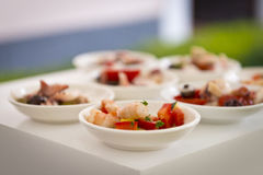 Shrimps and tomatoes finger food on aperitif Stock Photos