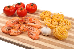 Shrimps, tomatoes and pasta Stock Photos