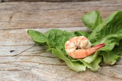 Shrimps with vegetables green leaves on wood background. Royalty Free Stock Image