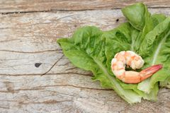 Shrimps with vegetables green leaves on wood background. Stock Photography