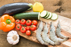 Shrimps with vegetables on wooden board Stock Images