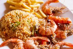 Shrimps on white plate over wooden table, served with rise and french fries, top view. Seafood concept.Selective focus stock image