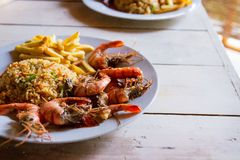 Shrimps on white plate over wooden table, served with rise and french fries, top view. Seafood concept.Selective focus. royalty free stock photo