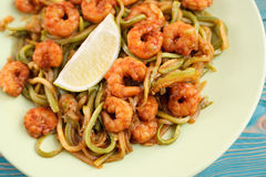 Shrimps and zucchini cut as noodles in green plate, close-up. Shrimps and zucchini cut as noodles in green plate, with lime slices, close-up, toned Royalty Free Stock Photography