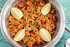 Shrimps and zucchini cut as noodles in pan, toned Stock Photos