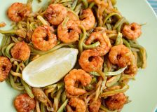 Shrimps and zucchini with lime in green plate, close-up. Toned Stock Photography