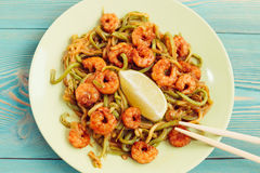 Shrimps and zucchini noodles in green plate on blue table Stock Image