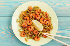 Shrimps and zucchini noodles in green plate on blue wooden table Royalty Free Stock Photography
