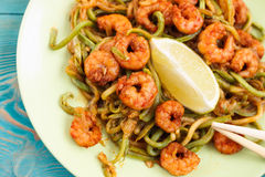 Shrimps and zucchini noodles in green plate, close-up. Shrimps and zucchini noodles in green plate, with lime slices, close-up, toned Stock Image