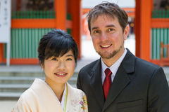Shrine Couple, International. An international couple, White and Japanese, pose in suit and kimono in front of a shrine for a 7-5-3 Ceremony; medium closeup Stock Photography