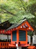Shrine lantern. Orange coloured shrine lantern with a maple tree branch hanging over it and the shrine in the background, in Arashiyama, Kyoto royalty free stock photos