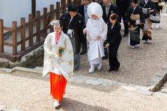 Shrine maiden leading wedding procession. A Shinto shrine maiden, called Miko, leading a wedding procession. Japan royalty free stock images