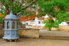 Shrine near Holy bodhi ficus tree in the Dambulla Golden temple. Cave complex buildinds carved in the rock is destination for pilgrims and tourists in Sri Lanka Royalty Free Stock Photos
