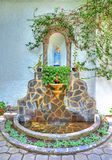 Shrine with a religious statue. Religious statue which is part of a shrine, adorned with stones, plants and its own water fountain. Outskirts of Quito, Pichincha Royalty Free Stock Images