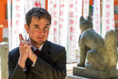 Shrine Spy. A man poses spyingly in front of a Japanese shrine wearing a suit royalty free stock images