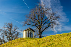 Shrine with three crosses on a green hill with blue sky. A religious shrine with three wooden crosses placed on a hill next to a leave-less tree. The sky is royalty free stock image