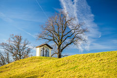 Shrine with three crosses on a green hill with blue sky. A religious shrine with three wooden crosses placed on a hill next to a leave-less tree. The sky is royalty free stock photography
