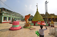 Shrines at Shwemawdaw Pagoda with a vendor carrying cut watermelon on the head Royalty Free Stock Images