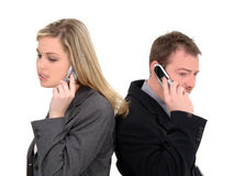 Shrinking World. Business man and woman back to back talking on cell phones, isolated over white Stock Photography