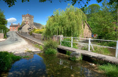 Shropshire Village, England. Diddlebury village in summer, showing the footbridge and church, Shropshire, England Stock Image