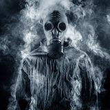 Shrouded in smoke. Man in a gas mask Royalty Free Stock Photo