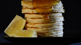 Shrove Tuesday breakfast with honey pouring over tall stack of pancakes stock video