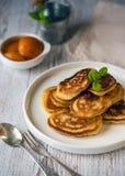 Shrove Wtorek, naleśnikowy dzień Bliny nalewający z miodem na tle talerze, rozwidlenia i noże rocznika, E zdjęcie stock