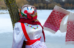 Shrovetide doll in colorful headscarf and sarafan near tree Stock Photo