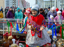 Shrovetide festivities. Cheerful woman-seller plays on wooden sp Royalty Free Stock Photography