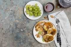 Shrovetide Maslenitsa Butter Week festival meal. Stack of pancakes blini with caramel with nuts, green grape, tea. Russian style, royalty free stock photo