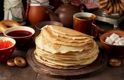 Shrovetide Maslenitsa Butter Week festival meal. Stack of russian pancakes blini. With red caviar, fresh sour cream and cranberry jam. Rustic style, close up royalty free stock photo