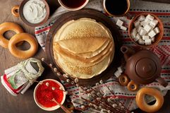 Shrovetide Maslenitsa Butter Week festival meal. Stack of russian pancakes blini. With red caviar, fresh sour cream, cranberry jam and sushki. Rustic style royalty free stock images