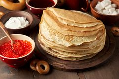 Shrovetide Maslenitsa Butter Week festival meal. Stack of russian pancakes blini. With red caviar, fresh sour cream and cranberry jam. Rustic style, close up stock photography